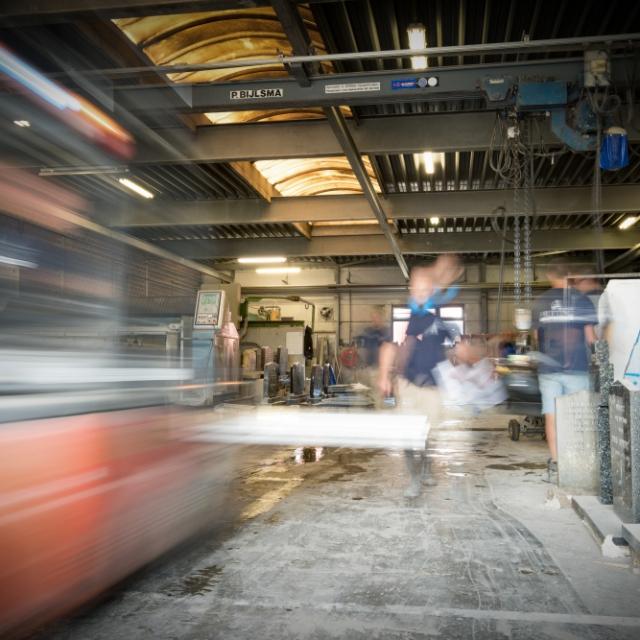 De grote werkplaats met bouwmachines van Hutting Natuursteen