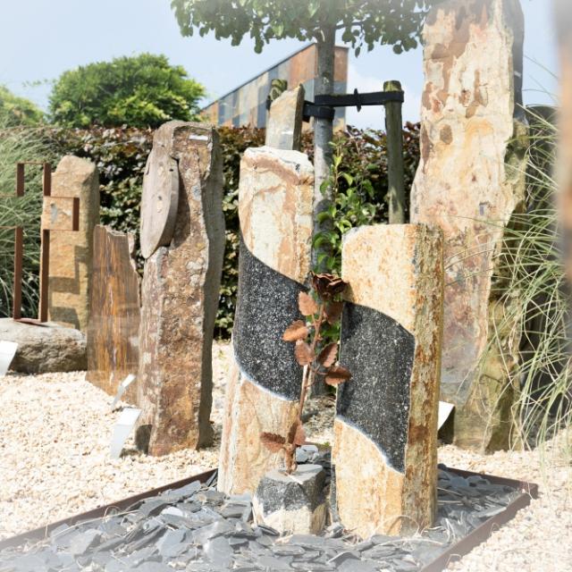 Basaltzuilen en morenekei met cortenstaal kruis in de monumententuin van Hutting Natuursteen